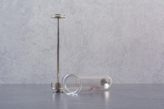 Części metalowej strzykawki na marmurowym stole.