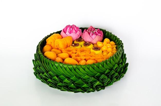 Częściowe skupienie się na tajskich deserach ślubnych na talerzu z liśćmi bananowca lub krathong na tajską tradycyjną ceremonię na białym tle.