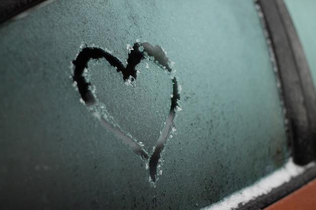 Częściowo niewyraźne serce narysowane palcem na zamarzniętym oknie pomarańczowego samochodu zimą, selektywna ostrość, kopia przestrzeń