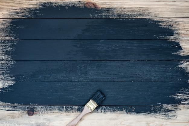 Częściowo pomalowane drewniane deski w czarnym tle. zabrudzona szczotka, proces. niedokończona praca.
