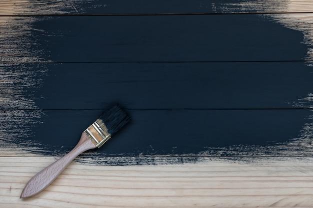 Częściowo pomalowane drewniane deski w kolorze czarnym. zabrudzona szczotka, proces. niedokończona praca. miejsce na tekst