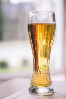 Częściowo zamazana szklanka jasnego piwa z bąbelkami, na drewnianym stole z białym obrusem w pobliżu okna. pionowy