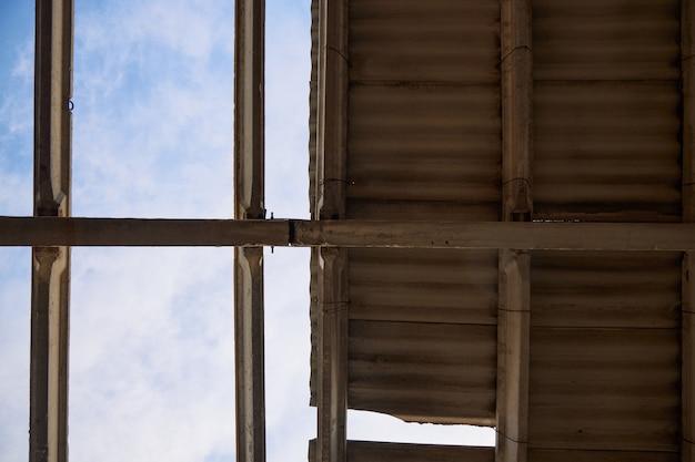 Częściowo zniszczony dach starego budynku, przez który widać błękitne niebo