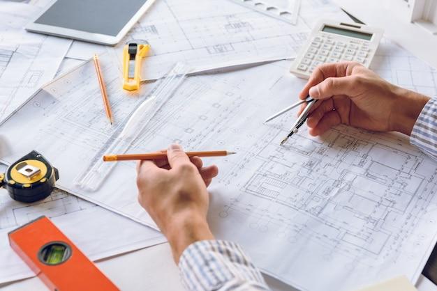 Częściowy widok architekta pracującego z planami nowego projektu budynku