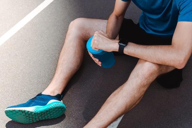 Częściowy widok sportowca w smartwatchie siedzącego na bieżni z butelką sportową