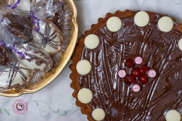 Częściowy widok z góry na ciasto czekoladowe i kosz z pisankami zawiniętymi w przezroczysty papier