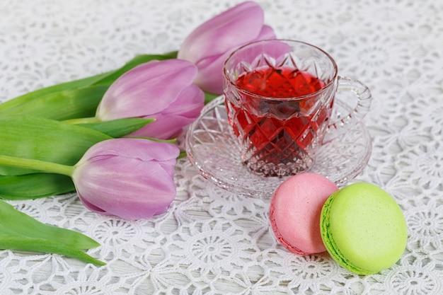 Czeski kryształowy przezroczysty kubek czerwonej herbaty karkadeh z ciasteczkami macarons i tulipanami z peri na pięknym szydełkowym obrusie