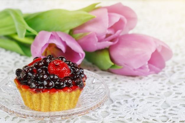Czeski kryształowy przezroczysty kubek czerwonej herbaty karkadeh z ciastem jagodowym i tulipanami na pięknym szydełkowym obrusie