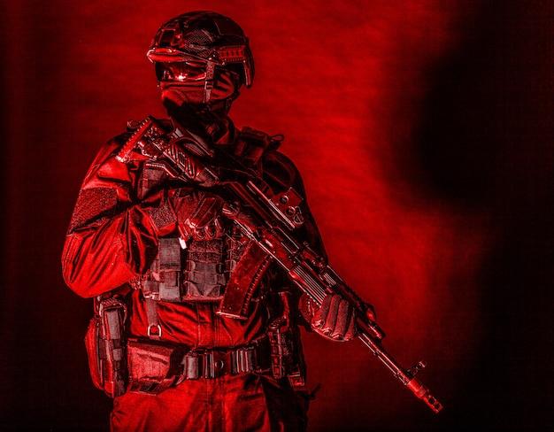Członek zespołu szturmowego policji, żołnierz sił specjalnych, prywatna służba bezpieczeństwa, żołnierz firmy wojskowej w czarnej amunicji i mundurze, karabin uzbrojony, strzelanie studyjne o wysokim kontraście na czarno