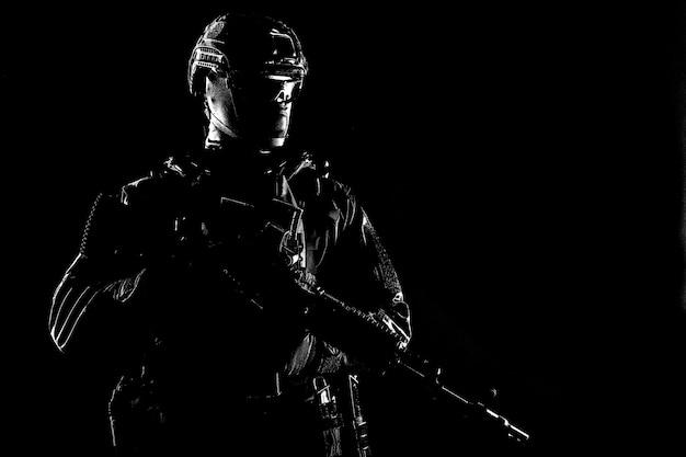 Członek zespołu taktycznego policji, siły specjalne armii, wojownik prywatnej firmy ochroniarskiej w czarnym mundurze, kasku i masce, celujący z kolimatorem na karabin szturmowy, stonowany na niebiesko, nisko kluczowa sesja studyjna