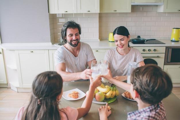 Członkowie jednej rodziny siedzą przy stole i trzymają razem szklanki mleka. oni się uśmiechają. rodzina ma śniadanie.