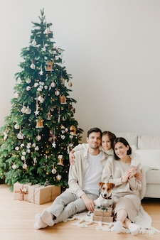 Członkowie rodziny pozują na podłodze w przytulnym pokoju, wokół znajdują się pudełka na prezenty, ozdobione choinkę i sofa.