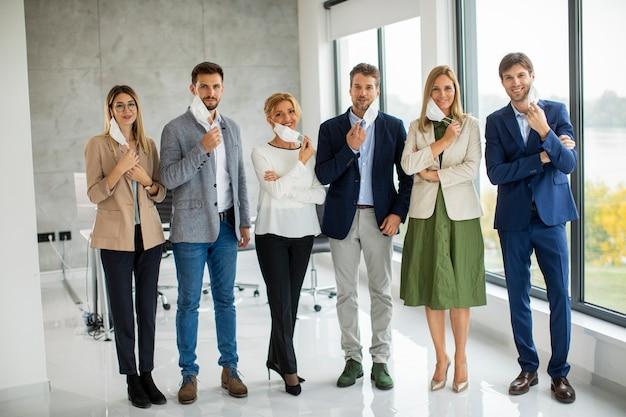 Członkowie zespołu biznesowego stoją w kolejce i zdejmują ochronne maski na twarz w biurze