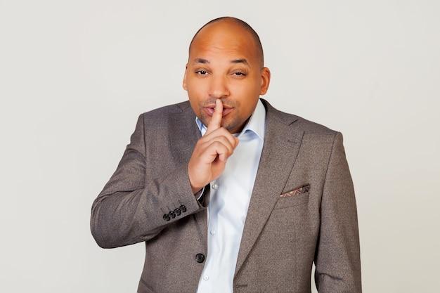 Człowiek afroamerykanin biznesmen w kurtce wykonuje gest ręką trzymając palec na ustach, prosi o ciszę i ciszę.