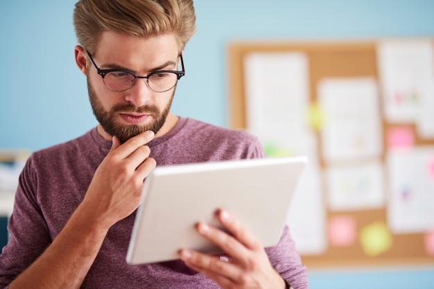 Człowiek bardzo skupiony na cyfrowym tablecie