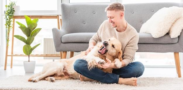 Człowiek bawi się z psem golden retriever, siedząc na podłodze w słonecznym mieszkaniu