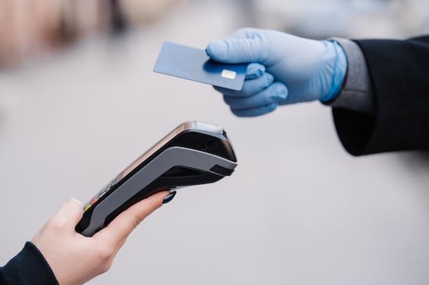 Człowiek bez twarzy w rękawiczkach medycznych podczas epidemii koronawirusa, trzyma plastikową kartę, próbuje dokonać bezgotówkowej zapłaty za bezpieczeństwo, wykorzystuje nowoczesną technologię. koncepcja pandemii, wirusów i zapobiegania