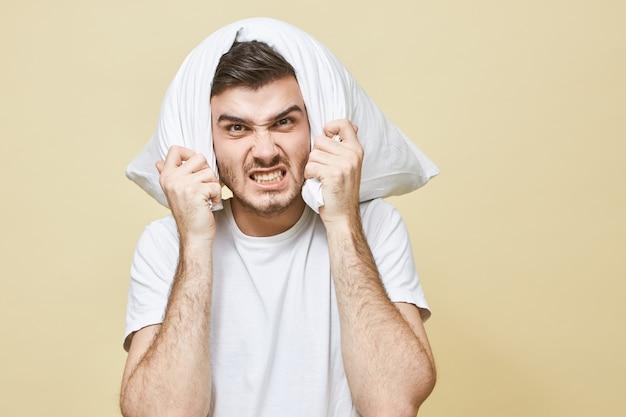 Człowiek bezsenność, brak snu i koncepcja problemu ze snem. przygnębiony młody mężczyzna z brodą zakrywającą uszy i głowę, próbujący zablokować głośny dźwięk alarmu lub obudzony w nocy przez hałaśliwego sąsiada