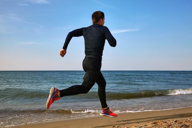 Człowiek biegacz nad brzegiem morza w stroju sportowym. bieganie kardio