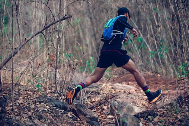 Człowiek biegacz szlaku. i stopy sportowca w sportowych butach do biegania po lesie