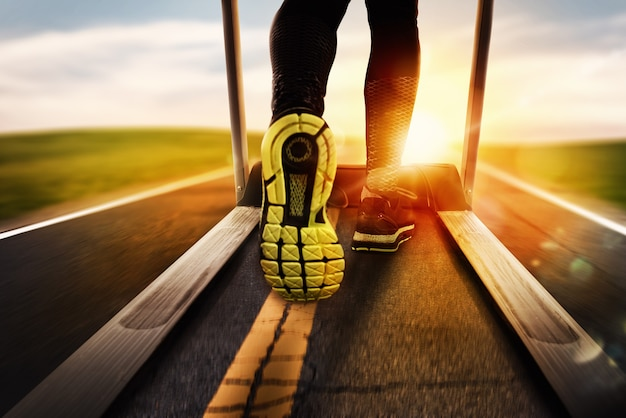 Człowiek biegnie z bieżni z asfaltu podczas wschodu słońca. koncepcja działania na świeżym powietrzu