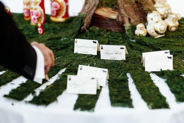 Człowiek bierze kartę ze swoim imieniem i nazwiskiem od stołu
