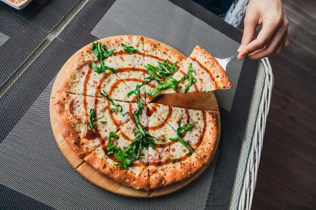 Człowiek bierze kawałek pizzy z całości na szarym tle w ulicznej kawiarni, widok z góry.