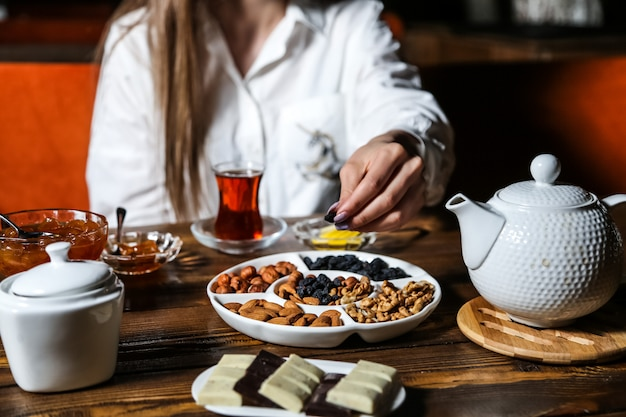 Człowiek bierze rodzynki z zestawu herbaty czekolada suszone owoce orzechy dżem widok z boku