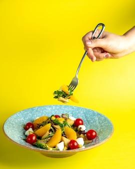Człowiek bierze sałatkę warzywną przez ludowy widok z boku