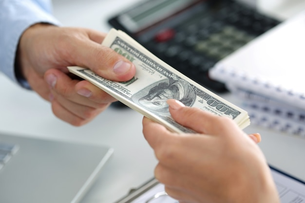 Człowiek biorąc partię stu dolarowych. ręce z bliska