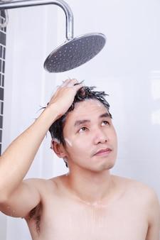 Człowiek biorąc prysznic ze strumieniem deszczowym i mycie włosów w łazience