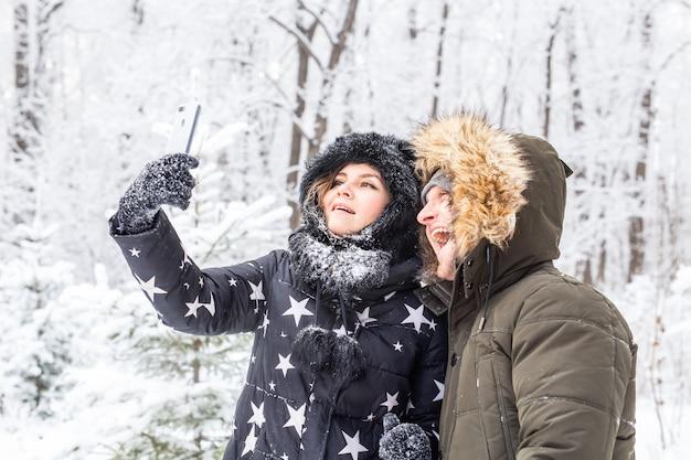 Człowiek biorąc selfie zdjęcie młoda para romantyczny uśmiech śnieg lasu zewnątrz zima.