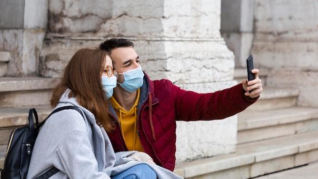 Człowiek biorąc selfie ze smartfonem na nim i jego dziewczyną w maskach