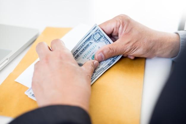 Człowiek biznesu liczenie pieniędzy przy stole