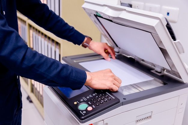Człowiek biznesu ręcznie nacisnąć przycisk na panelu drukarki.