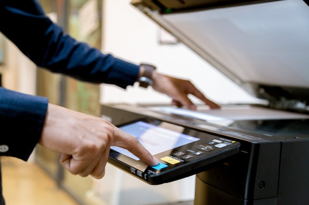 Człowiek biznesu ręka naciśnij przycisk na panelu drukarki.