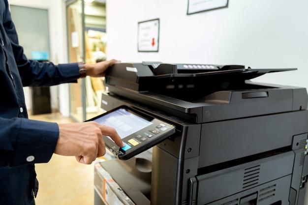 Człowiek biznesu ręka naciśnij przycisk na panelu drukarki