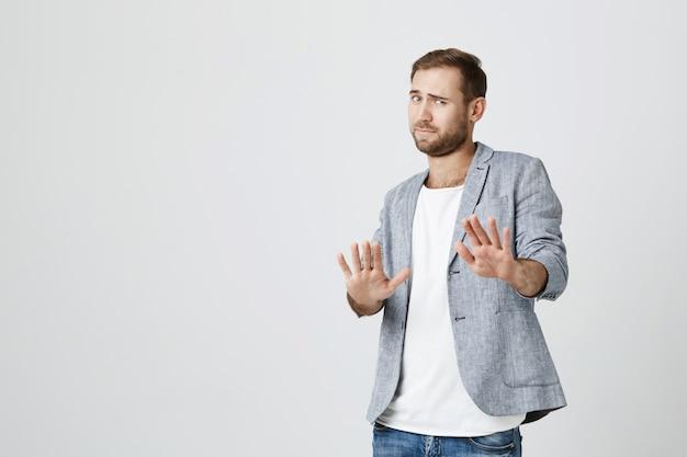Człowiek broni się przed kimś, pokaż gest stopu
