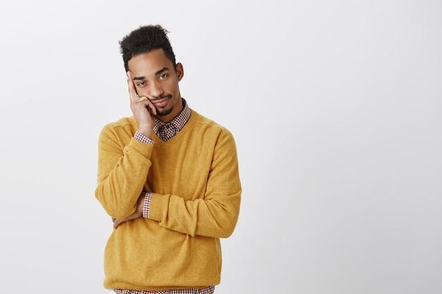 Człowiek chce być gdzie indziej. zaniepokojony atrakcyjny młody mężczyzna z fryzurą afro, opierający głowę na dłoni, znudzony i obojętny, wyrażający chęć odejścia i irytację na szarej ścianie