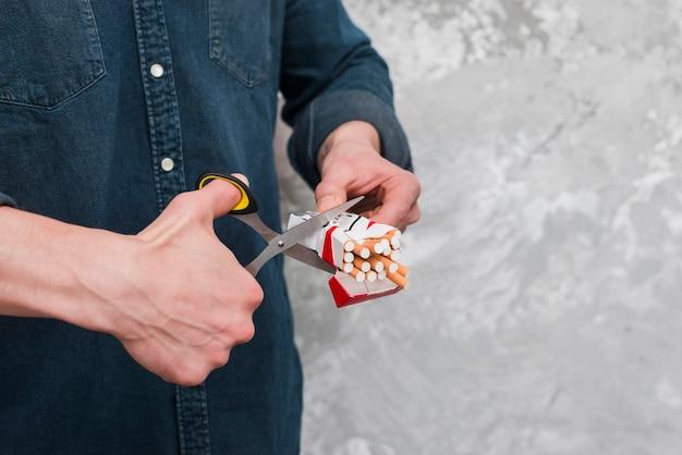 Człowiek cięcia pudełko papierosów z nożyczek