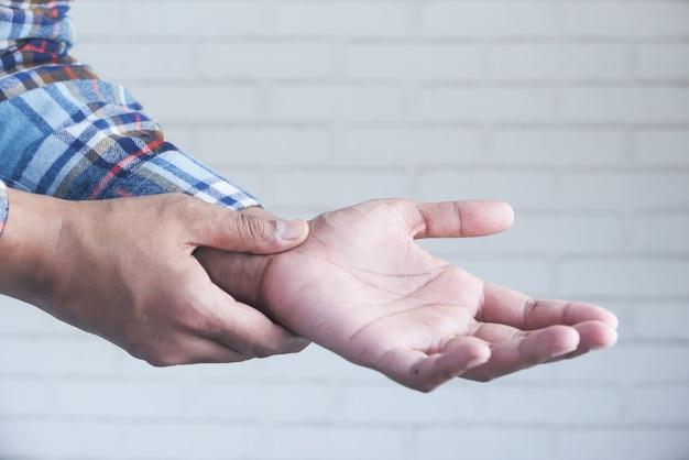 Człowiek cierpi na ból w dłoni z bliska.