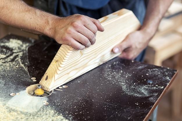 Człowiek cieśla przetwarza krawędzie drewnianego produktu za pomocą frezarki, zbliżenie
