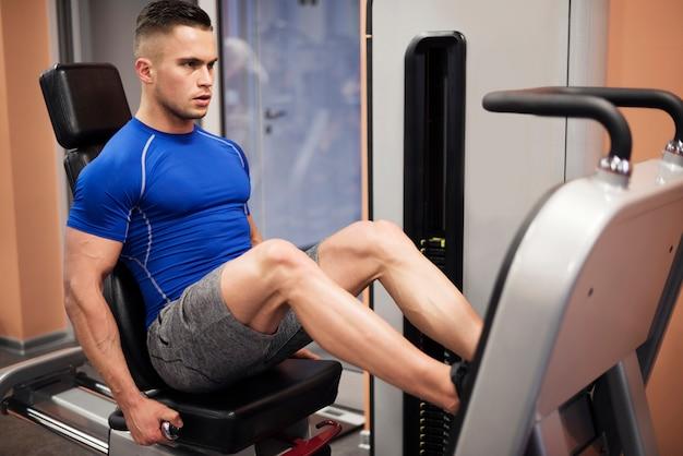 Człowiek ćwiczy na maszynie prasy nogi