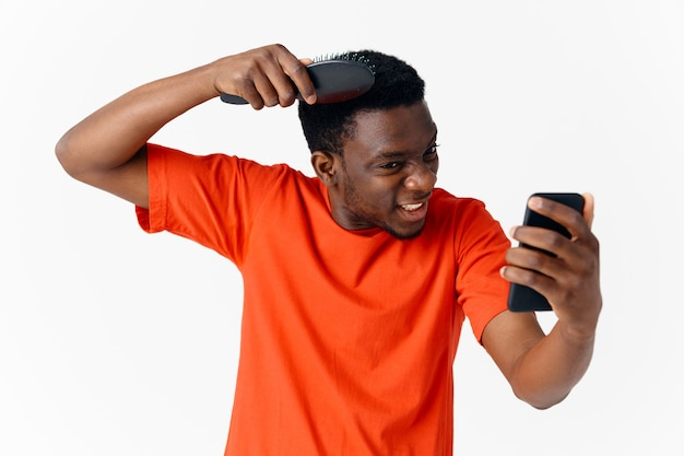 Człowiek czesanie głowę z telefonem w jego ręce opieki głowy na białym tle. zdjęcie wysokiej jakości