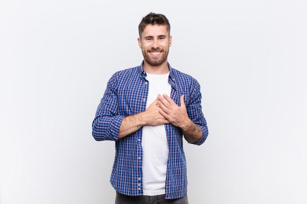 Człowiek czuje się romantyczny, szczęśliwy i zakochany, uśmiecha się wesoło i trzyma ręce blisko serca