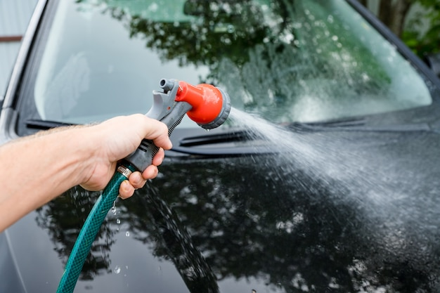 Człowiek czyszczenia swojego samochodu w samoobsługowej myjni samochodowej, szczotki pozostawiając uderzenia szamponem