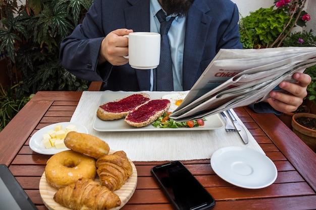 Człowiek czyta gazetę przy śniadaniu
