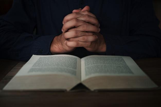 Człowiek czyta pismo święte lub pismo święte i modli się na nim na drewnianym stole z miejscem na kopię. religia, uwierz koncepcja.