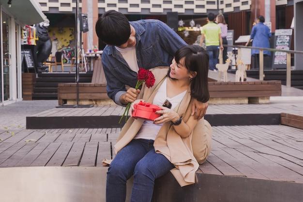 Człowiek daje kwiaty z dziewczyną na ulicy