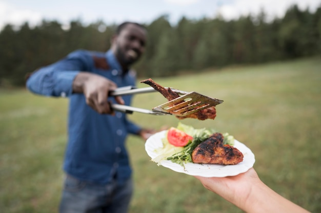 Człowiek daje stek osobie na grilla